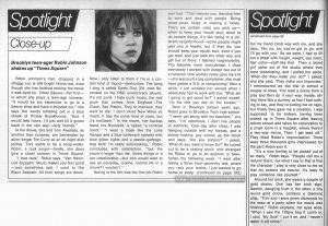 "Edwin Miller's ""Spotlight"" column featured a ""Close-up"" on Robin Johnson on pages 98 and 100. Text: Spotlight Close-up Brooklyn teen-ager Robin Johnson shakes up ""Times Square"" Robin Johnson's hair, chopped in a shaggy cut. is still bright henna-red. even though she has finished making the movie it was dyed for. Times Square—her first- in which she plays a teen-age runaway. ""It would be too expensive to go to a beauty shop and have it stripped out."" she says, her words tumbling out in a blue streak of throaty Brooklynese. ""And it would take hours. I'll just wait till it grows back in the real way—dirty blonde."" In the movie, she and Trini Alvarado, as another teen runaway, arc befriended by actor-singer Tim Curry as an all-night disk jockey. Trini wants to be a song-writer. Robin, a rock singer—finally, she does give a street concert in Times Square. ""I love rock."" Robin says. ""Van Halen. Led Zeppelin. Music makes you feel good —and sometimes sad. I used to like Black Sabbath. All their songs are doom. Now I only listen to them if I'm in a certain kind of mood—destructive. The song I sing is called Damn Dog [Ed. note:Recorded on the RSO sound-track album]. It's not punk. I hate punk music, the real punk that comes from England—The Clash. Sex Pistols. They're maniacs: they want to die. I don't mind New Wave so much. It has the same kind of roots, but it's mellower."" In the movie, her backup band, the Blondells, is called ""a criminal band."" ""I v/ear a mask like the Lone Ranger and a blue turtleneck sweater with blue glitter tights and a plastic-garbage- bag belt! I'm really wild-looking."" Robin concludes v/ith satisfaction, ""but the movie's larger than life. Some things in it are unbelievable—but who would want to see an everyday, routine, normal life in a movie? I wouldn't."" Acting in the film was the first job Robin ever had. ""That matures you. learning how to work and deal with people. Being street-smart helps in making a movie. There are certain rules you pick up— when to keep your mouth shut, when to do certain things. It's like being in a different neighborhood—some people might give you a hassle, but if they do. you should keep your mouth shut, even if you get mad. and just walk the other way and get out of there. I learned responsibility. You become more considerate. I liked everybody I worked with except two out of a hundred. One woman really gave me a fit —she was such a big complainer. she must have gotten a B.A. in complaining! After a while. I just avoided her except when I absolutely had to work with her. 'What am I going to get upset for?' I asked myself. 'I'm the one you see on the screen.'"" Born in Brooklyn sixteen years ago, Robin goes to Brooklyn Tech high school. ""I never get along with my teachers."" she says. ""I'm rebellious. I don't like people in authority. One day after class. I was hanging outside with my friends, and a skinny-looking guy comes up the block and says. 'Are you sixteen?' I asked, What do you want to know for?' He turned out to be a casting scout, who arranged for Robin to go to an audition in Manhattan the following week. ""I went after taking a three-hour geometry test, where you rack your brains. I just wanted to go home to sleep (continued on page 100) Spotlight continued from page 98 but my friend Cindi was with me. and she says. 'No. no. no. you've got to go. and I'll go with you.' So we went. I had to fill out a sheet with height, weight, eye color, hair color—stuff like that. Then a blond girl came out of the studio where they were videotaping, and I pulled her aside. 'What did they make you do?' I asked, and she said. 'They make you improvise.' I remembered we did that in school a couple of times. You read a scene from a play and then do it your way. Inside, sitting there like a dummy, at first I had nothing to say. and they're putting me on tape, but finally they gave me a situation. I was supposed to be sixteen, having been picked up in Times Square after leaving reform school and taken for observation to a small room in a hospital, where there's a two-way mirror. Then I get teed off."" They liked Robin's improvisation. There were three thousand girls interviewed for the part; Robin won it. ""It's a nice feeling to be picked out of so many."" Robin says. ""People call me a natural talent, but what I say to that is that the character I play is very close to me so that my actions are natural. It's easy to play someone like yourself."" Around her neck, she wears a couple of gold chains. One has her birth sign. Gemini, dangling from it; the other, a tiny round gold circle, contains a diamond chip. ""Trimi and I were given diamonds by the crew at a party when the movie was finished,"" Robin explains, her eyes wide. ""When I saw the Tiffany bag it came in. I said. 'My God!' I put it on, and I haven't taken it off since."""
