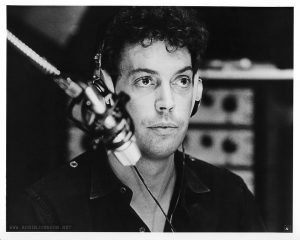 Tim Curry as Johnny LaGuardia in the WJAD studio, in the UK press kit photograph numbered 4. The text from the press kit's photo captions page: 4. TIM CURRY stars as an all-night disc jockey, who, perched in his studio high above Times Square follows and encourages the progress of the runaway girls, who thanks to his efforts become minor media celebrities.