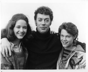 "Trini Alvarado, Robin Johnson, and Tim Curry in a rare glamor shot, outside on or near Pier 56, in an unnumbered print from the ""Times Square"" UK press kit. The photo is identified by a code that matches the US publicity photos style, TS-88-29A. None of the captions on the caption sheet match up with the image. The caption list omits numbers 9 and 10; however, there are three unidentified photos in this copy of the press kit. Two of them (including this one) have US-style code numbers."