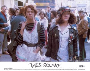 "Robin Johnson and Trini Alvarado as Nicky and Pammy, on 42nd Street near 6th Avenue: Color 8""x10"" lobby card, 1981 Text: TIMES SQUARE AA Released by COLUMBIA - EMI - WARNER Distributors Limited. EMI A Member of the THORN EMI Group An EMI-ITC Production This copyright advertising material is licensed and not sold and is the property of National Screen Service Ltd. and upon completion of the exhibition for which it has been licensed it should be returned to National Screen Service Ltd. Printed in Great Britain."
