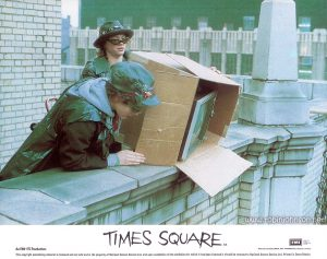 "Color 8""x10"" lobby card, 1981: Pammy and Nicky drop a television off the roof of a New York City building. Text: TIMES SQUARE AA Released by COLUMBIA - EMI - WARNER Distributors Limited. EMI A Member of the THORN EMI Group An EMI-ITC Production This copyright advertising material is licensed and not sold and is the property of National Screen Service Ltd. and upon completion of the exhibition for which it has been licensed it should be returned to National Screen Service Ltd. Printed in Great Britain."