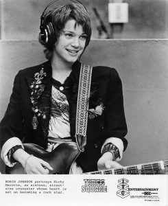 Robin Johnson as Nicky Marotta in the WJAD studio.  ITC variant of TIMES SQAURE press photo TS-69-34A.  Text:  ROBIN JOHNSON portrays Nicky  Marotta, an aimless, street- wise youngster whose heart is  set on becoming a rock star.  TIMES SQUARE™  ITC ENTERTAINMENT AN acc COMPANY  Permission is hereby granted to newspapers and other periodicals to reproduce this photograph for publicity or advertising except for the endorsement of products.  This must not be sold leased or given away.  Printed in U.S.A.