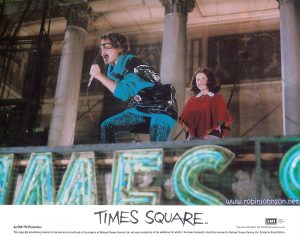 "UK Lobby Card 8 of 8: The Concert in Times Square. Color 8""x10"" lobby card, 1981: Pammy watches as Nicky sings ""Damn Dog"" atop the TImes Square Theater marquee. Text: TIMES SQUARE AA Released by COLUMBIA - EMI - WARNER Distributors Limited. EMI A Member of the THORN EMI Group An EMI-ITC Production This copyright advertising material is licensed and not sold and is the property of National Screen Service Ltd. and upon completion of the exhibition for which it has been licensed it should be returned to National Screen Service Ltd. Printed in Great Britain."