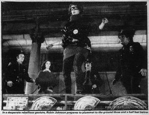 Photo accompanying review of TIMES SQUARE in New Muscial Express, 24 January 1981, page 14.  Caption: In a desperate rebellious gesture, Robin Johnson prepares to plummet to the ground three and a half feet below.   Text:  Page 14 — New Musical Express 24th January, 1981  I