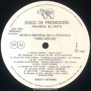 """Disc 1, Side 1 of the Peruvian edition of the soundtrack to TIMES SQUARE (1980) Text: RESERVADOS TODOS LOS DERECHOS DEL PRODUCTOR FONOGRAFICO Y DEL PROPRIETARIO DE LA OBRA REGISTRADA RSO DISCO DE PROMOCION PROHIBIDA SU VENTA A25 - RSO 2658145.3 STEREO MUSICA ORIGINAL DE LA PELICULA """"TIMES SQUARE"""" ST 33 1 ® 1980 1. ROCK HARD - """"Rock hard"""" - (M. Chapman - N. Chinn) (3:18) - SUZI QUATRO 2. TALK OF THE TOWN - """"Habladuría del pueblo"""" - (C. Hynde) (3:16) - THE PRETENDERS 3. SAME OLD SCENE - """"Misma vieja escena"""" - (B. Ferry) (3:54) - ROXY MUSIC 4. DOWN IN THE PARK - """"Abajo en el parque"""" - (G. Numan) (4:20) - GARY NUMAN 5. HELP ME - """"Ayúdenme"""" - (R. Gibb - B. Weaver) (3:27) - MARCY LEVY AND ROBIN GIBB DISCO 1 (2479264) MANUFACTURADO POR """"EL VIRREY"""" INDUSTRIAS MUSICALES S.A. INDUSTRIA PERUANA REG. IND. 12428"""