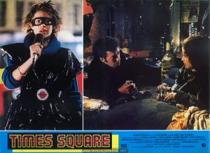 "Two images from the film TIMES SQUARE (1980); ((1) Robin Johnson (2) Tim Curry and Trini Alvarado) with accompanying text:  TIMES SQUARE ROBERT STIGWOOD presenta ""TIMES SQUARE""con TIM CURRY • TRINI ALVARADO  e per la prima volta sullo schermo ROBIN JOHNSON con PETER COFFIELD • HERBERT BERGHOF • DAVID MARGULIES  ANNA MARIA HORSFORD  produttori esecutivi KEVIN McCORMICK e JOHN NICOLELLA  diretto da ALAN MOYLE  prodotto da ROBERT STIGWOOD e JACOB BRACKMAN  sceneggiatura di JACOB BRACKMAN  soggetto di ALAN MOYLE e LEANNE UNGER EMI  produttore associato BILL OAKES  una produzione EMI-ITC  Technicolor • STEREOFUTURSOUND  IDIF"