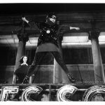 "Robin Johnson as Nicky Marotta leaps into the the air, beginning her performance at the conclusion of ""Times Square"" (1980). This specific shot does not, however, appear in the film; it is part of a series of publicity stills that replicate events from the film but do not actually appear in it. The equivalent shot in the film is much closer in and Nicky's face is turned in the opposite direction. Inscription: ""34"" at bottom right. [On back:] [stamped, black:] TIMES SQUARE [handwritten, black:] 34 [handwritten, blue:] Robin Johnson, Trini Alvarez"