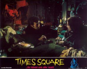 Tim Curry as Johnny LaGuardia and Trini Alvarado as Pamela Pearl Text at bottom: schröder-filmverleih TIMES SQUARE ...ihr könnt uns alle 'mal!! FSK FREIGEGEBEN