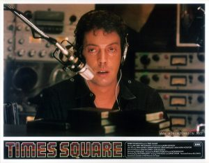 "TIMES SQUARE UK lobby card set 1, 1981, 1 of 16: Tim Curry as Johnny LaGuardia in the WJAD studio Text: TIMES SQUARE ™ ROBERT STIGWOOD Presents ""TIMES SQUARE"" EMI Starring TIM CURRY • TRINI ALVARADO And Introducing ROBIN JOHNSON Also Starring PETER COFFIELD • HERBERT BERGHOF • DAVID MARGULIES • ANNA MARIA HORSFORD Executive Producers KEVIN McCORMICK • JOHN NICOLELLA Directed by ALAN MOYLE Produced by ROBERT STIGWOOD and JACOB BRACKMAN Screenplay by JACOB BRACKMAN Story by ALAN MOYLE and LEANNE UNGER Associate Producer BILL OAKES Soundtrack available on RSO Records ond Tapes"