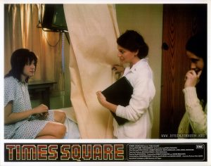 "TIMES SQUARE UK lobby card set 1, 1981, 2 of 16: Nurse Joan introduces Pammy and Nicky. Text: TIMES SQUARE ™ ROBERT STIGWOOD Presents ""TIMES SQUARE"" EMI Starring TIM CURRY • TRINI ALVARADO And Introducing ROBIN JOHNSON Also Starring PETER COFFIELD • HERBERT BERGHOF • DAVID MARGULIES • ANNA MARIA HORSFORD Executive Producers KEVIN McCORMICK • JOHN NICOLELLA Directed by ALAN MOYLE Produced by ROBERT STIGWOOD and JACOB BRACKMAN Screenplay by JACOB BRACKMAN Story by ALAN MOYLE and LEANNE UNGER Associate Producer BILL OAKES Soundtrack available on RSO Records ond Tapes"