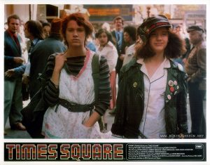 "TIMES SQUARE UK lobby card set 1, 1981, 3 of 16:Nicky and Pammy on the road to Times Square. Text: TIMES SQUARE ™ ROBERT STIGWOOD Presents ""TIMES SQUARE"" EMI Starring TIM CURRY • TRINI ALVARADO And Introducing ROBIN JOHNSON Also Starring PETER COFFIELD • HERBERT BERGHOF • DAVID MARGULIES • ANNA MARIA HORSFORD Executive Producers KEVIN McCORMICK • JOHN NICOLELLA Directed by ALAN MOYLE Produced by ROBERT STIGWOOD and JACOB BRACKMAN Screenplay by JACOB BRACKMAN Story by ALAN MOYLE and LEANNE UNGER Associate Producer BILL OAKES Soundtrack available on RSO Records ond Tapes"