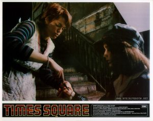 "TIMES SQUARE UK lobby card set 1, 1981, 4 of 16: Nicky and Pammy share bad blood. Text: TIMES SQUARE ™ ROBERT STIGWOOD Presents ""TIMES SQUARE"" EMI Starring TIM CURRY • TRINI ALVARADO And Introducing ROBIN JOHNSON Also Starring PETER COFFIELD • HERBERT BERGHOF • DAVID MARGULIES • ANNA MARIA HORSFORD Executive Producers KEVIN McCORMICK • JOHN NICOLELLA Directed by ALAN MOYLE Produced by ROBERT STIGWOOD and JACOB BRACKMAN Screenplay by JACOB BRACKMAN Story by ALAN MOYLE and LEANNE UNGER Associate Producer BILL OAKES Soundtrack available on RSO Records ond Tapes"