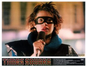 "Nicky has one more thing to say, one more thing. Text: TIMES SQUARE ™ ROBERT STIGWOOD Presents ""TIMES SQUARE"" EMI Starring TIM CURRY • TRINI ALVARADO And Introducing ROBIN JOHNSON Also Starring PETER COFFIELD • HERBERT BERGHOF • DAVID MARGULIES • ANNA MARIA HORSFORD Executive Producers KEVIN McCORMICK • JOHN NICOLELLA Directed by ALAN MOYLE Produced by ROBERT STIGWOOD and JACOB BRACKMAN Screenplay by JACOB BRACKMAN Story by ALAN MOYLE and LEANNE UNGER Associate Producer BILL OAKES Soundtrack available on RSO Records and Tapes"
