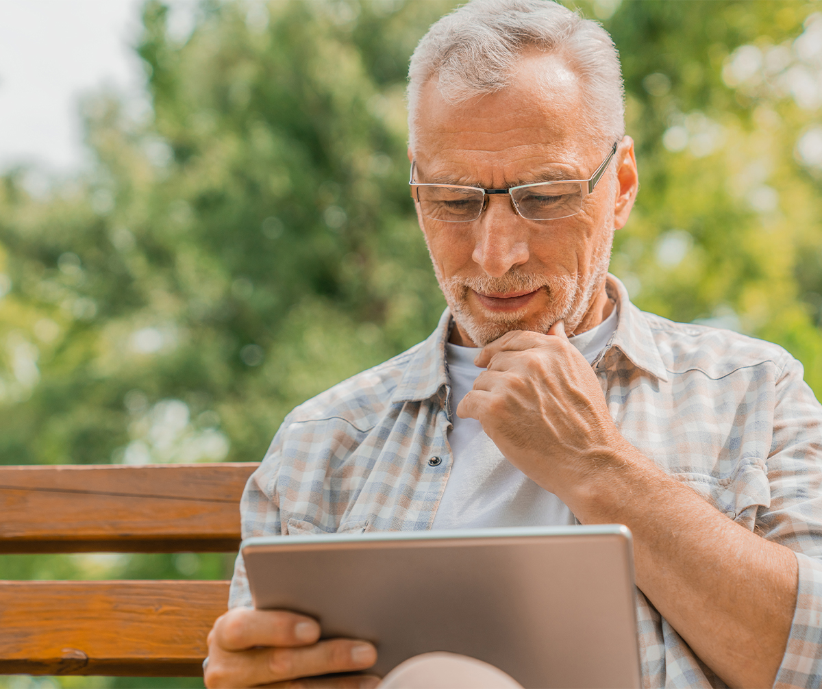 older man sitting on a bench outside and reading an ipad