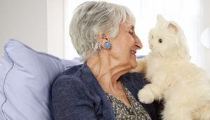 old woman with robotic pet car on shoulder cant care for pet