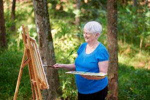 Senior woman painting outside at Rolling Green Village