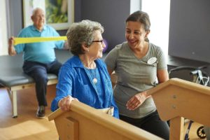 elderly woman doing physical therapy with younger woman in greenville sc rehab facility