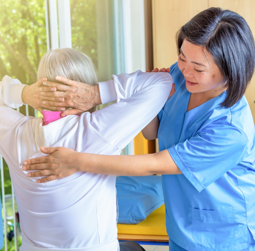 Female physical therapist helping senior woman in rehab