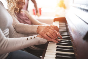 elderly woman and younger woman playing piano together