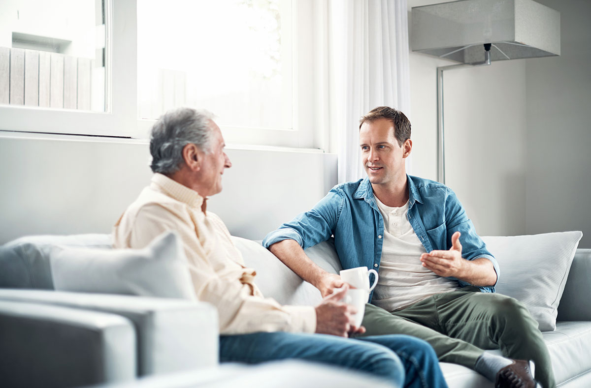 younger man talking to elderly parent about changes while sitting on couch