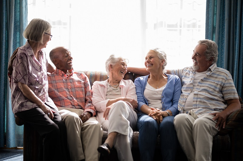 a group of seniors enjoying social time on a couch at a independent living community
