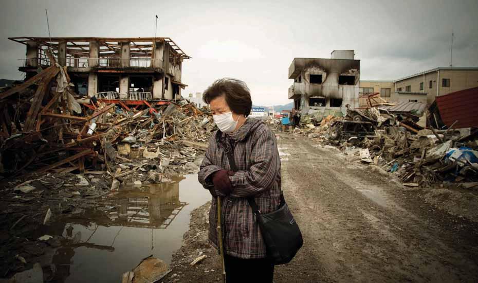 Fukushima, elderly woman surveys the wreckage following the enormous tsnuami that destroyed the coastline