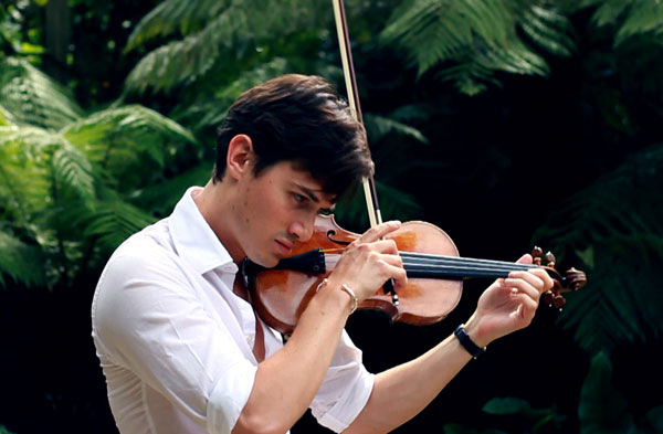 Charlie Siem playing his violin in his garden