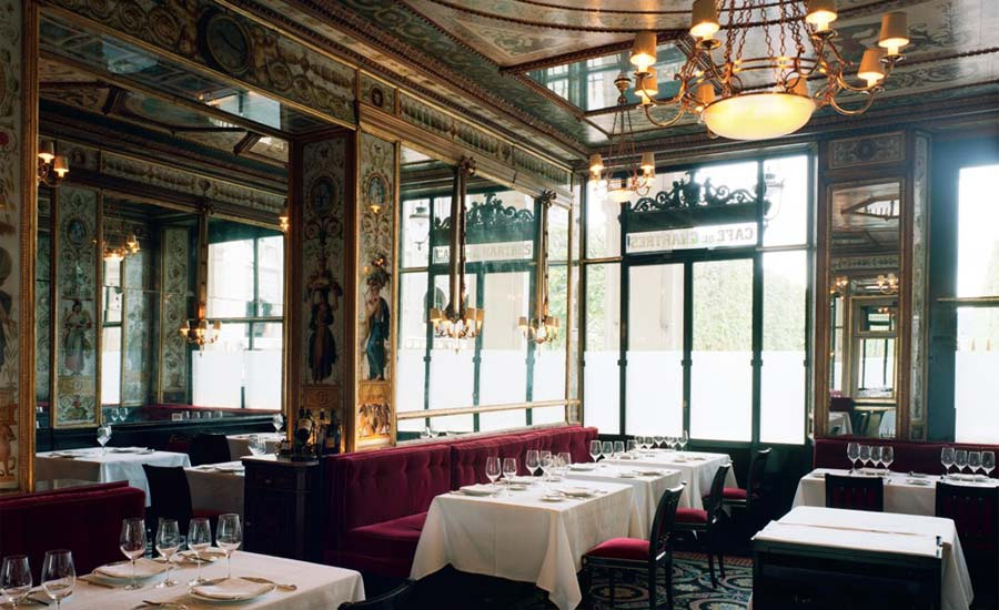 Interior of Le Grand Vefour, Paris – a chandelier hangs from an orate ceiling down onto a room filled with white linen laid tables.