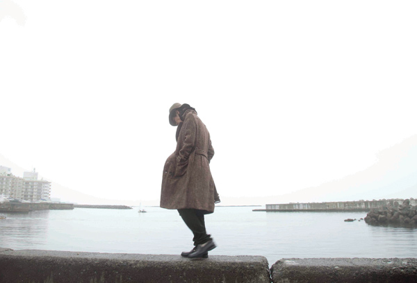 Ryo walking along a sea wall