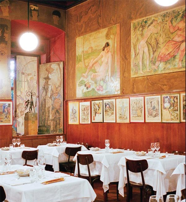 Interior shot of Bagutta restaurant, Milan showing crisp white linen laid over wooden tables, set against a backdrop of the restaurant's red walls (hung with a dozen framed paintings)