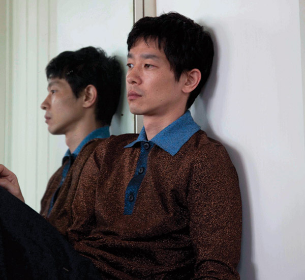 Ryo sits next to his reflection in the mirror. He is wearing a Lurex polo shirt by Prada