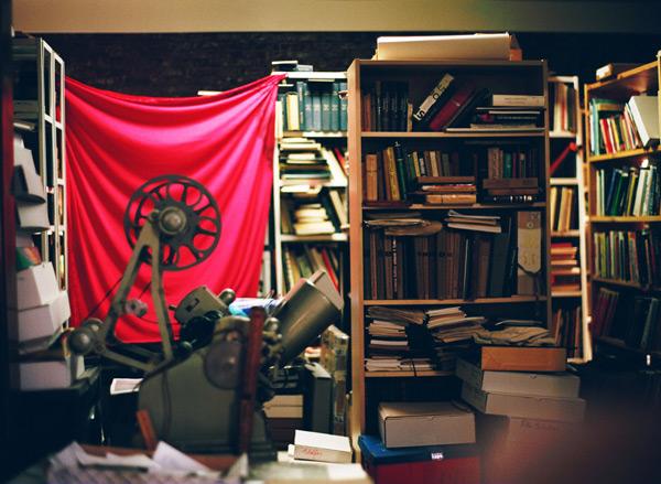 Jonas-Mekas-Studio view - film reels, projector and Archive flag hanging