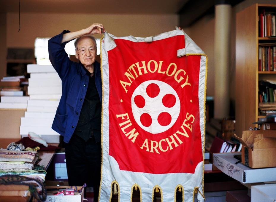 Jonas-Mekas-holding his AFA banner in his studio
