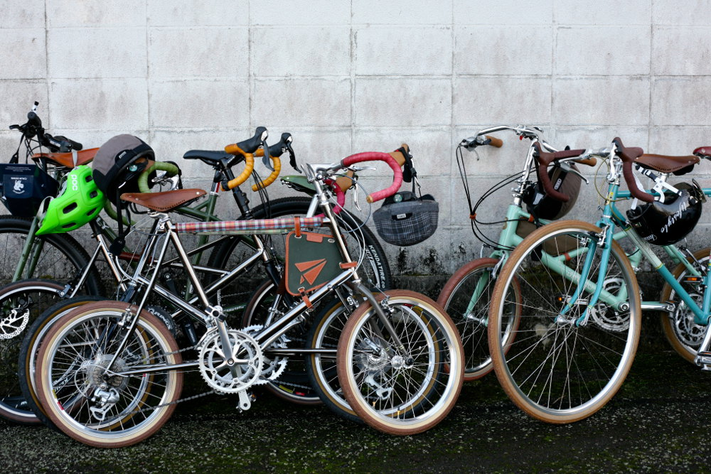 Bikes are parked against a wall while Tour de Nippon riders take a well-earned rest