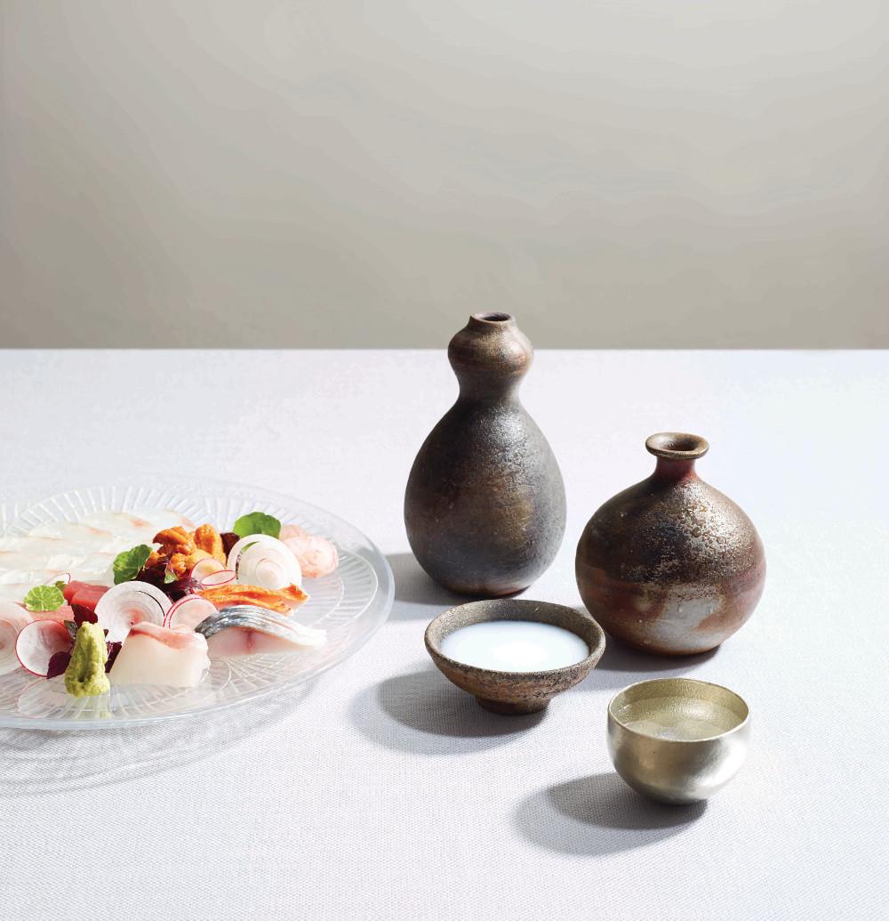 Omakase Sashimi prepared by Chef Yoshinori Ishii of Umu, with line-caught Cornish ikejime, streaked gurnard usuzukuri, stone bass, red mullet, mackerel, Icelandic sea urchin and toro. Plate: René Lalique 'Coquille' from 1910 Sakes: Bijofu Schwa (sparkling) Kamoizumi Nigori (cloudy/nigori) Kamoshibito Kuheiji Junmai Daiginjo 50 (regular)