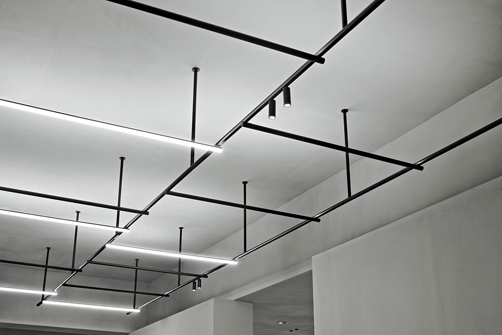 'Infra-Structure' uses FLOS's innovative magnetic system  to allow an endless configuration of spotlights, lamps and ceiling facing strip lights