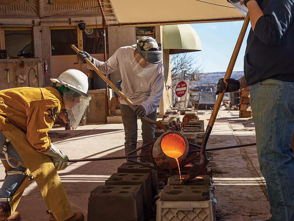 Workers pour molten bronze, heated to 1,315ºC, into sand moulds. The green umbrella in the background collects waste heat from the furnace to warm the surrounding residential apartments