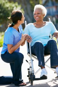 nurse helping senior woman in wheel chair