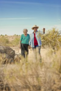 two seniors walk through a desert trail together in phoenix
