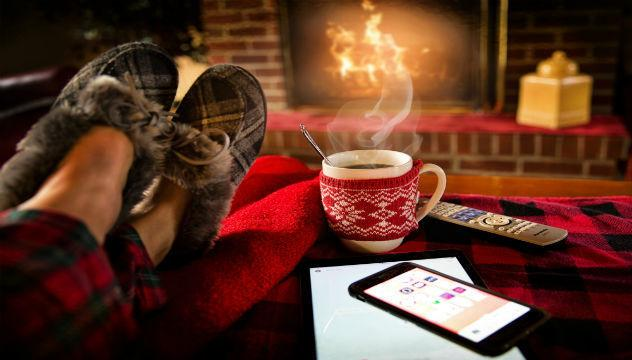 person with their feet up on front of a cozy fire with a hot drink