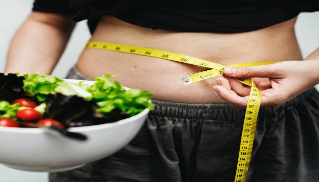 person measuring their waist holding a bowl of salad