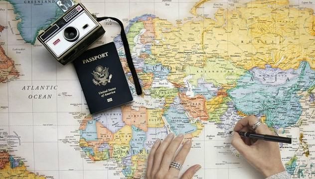 person planning a travel tour with a map and passport