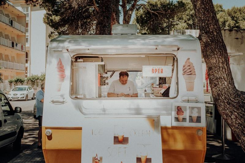 A Man in a White Food Truck Selling Ice Cream on the Side of a Street