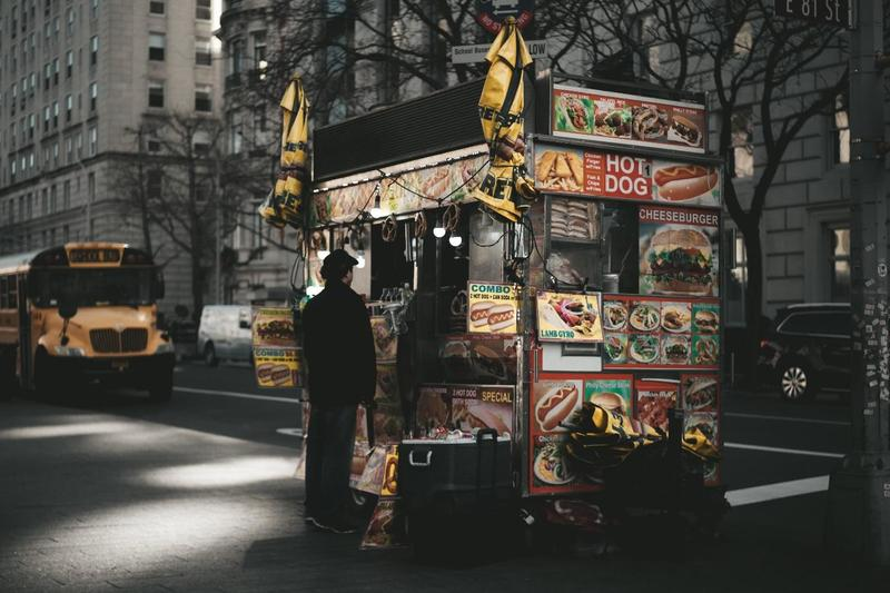 a customer ordering from a hot dog labelled food truck