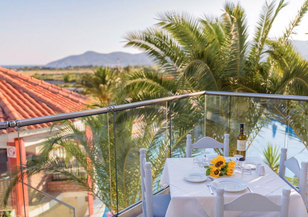 Τραπέζι στο μπαλκόνι του δωματίου με πιάτα και κρασί και θέα το νησί