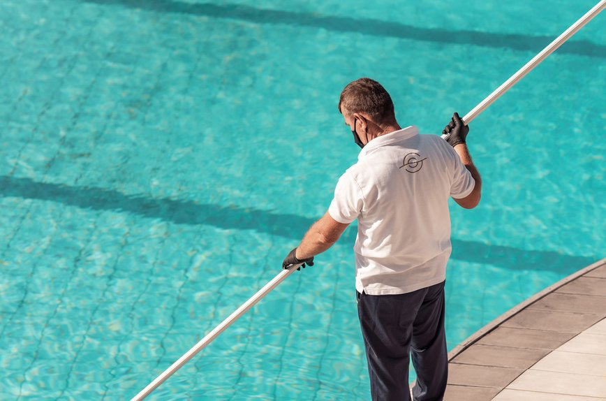 Employee cleaning the pool wearing mask and gloves