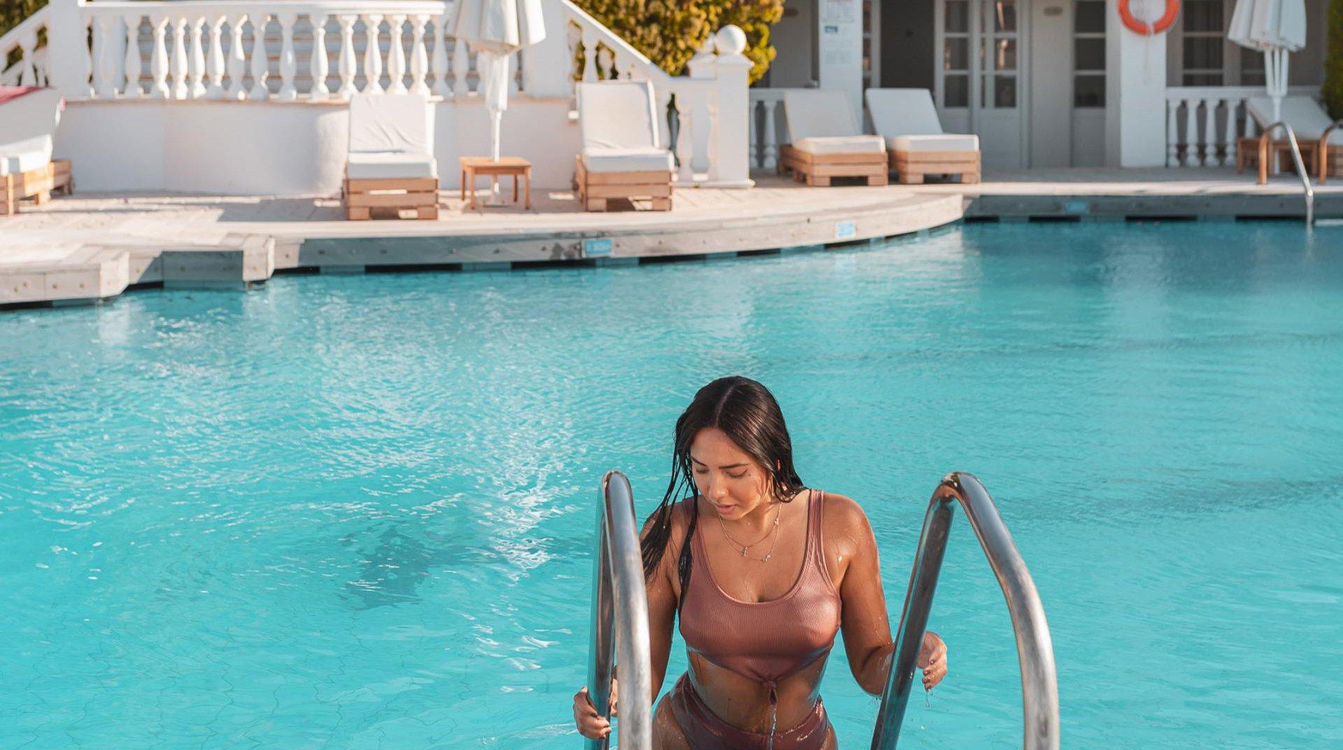 Γυναίκα βγαίνει από την πισίνα με το ξενοδοχείο μας στο φόντο