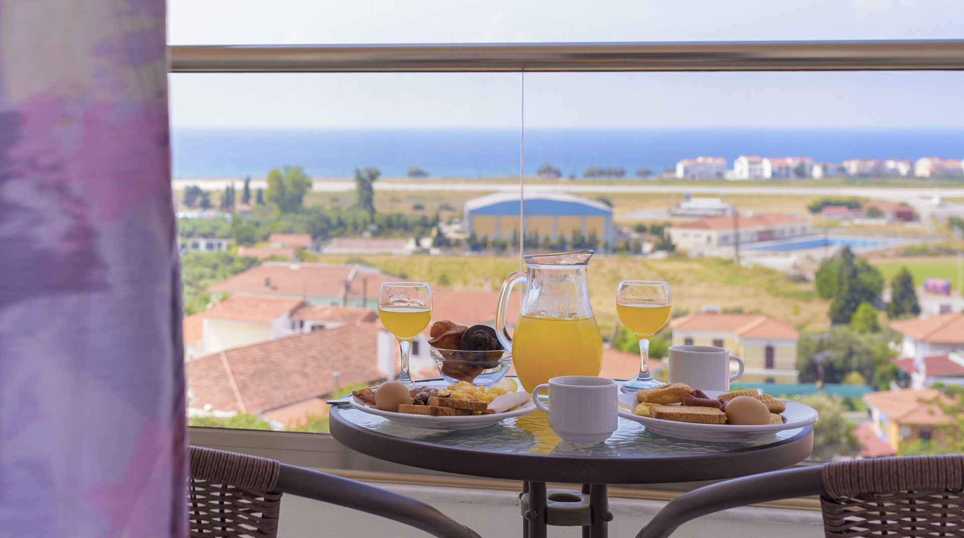 Table at the balcony of our room with plates full of our delicious breakfast and juice looking at the sea