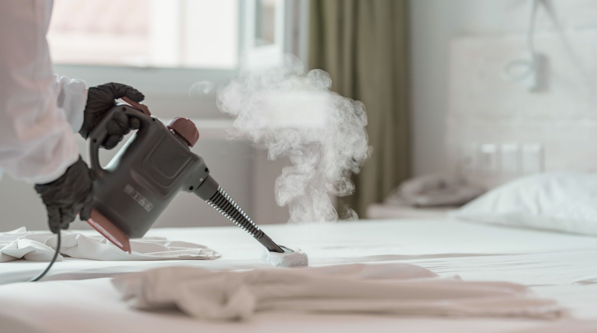 Employee steam cleaning the beds wearing mask and gloves