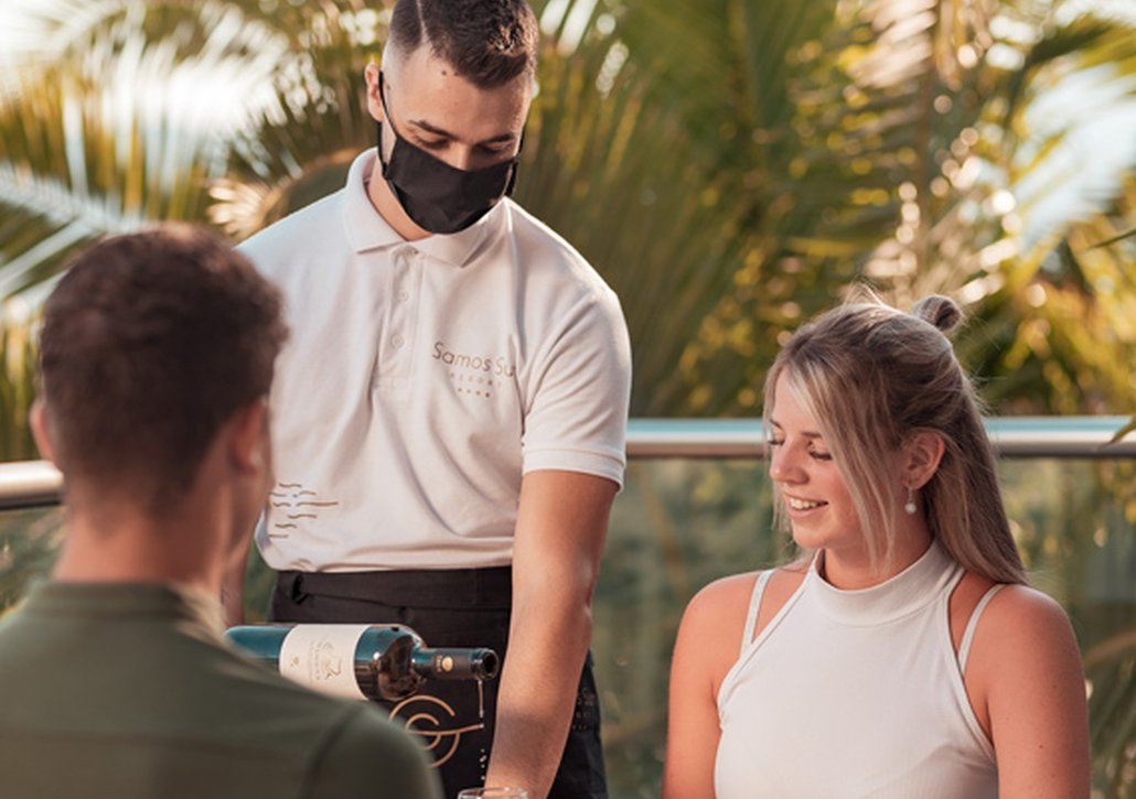 Σερβιτόρος να σερβίρει πελάτες φορώντας μάσκα και γάντια